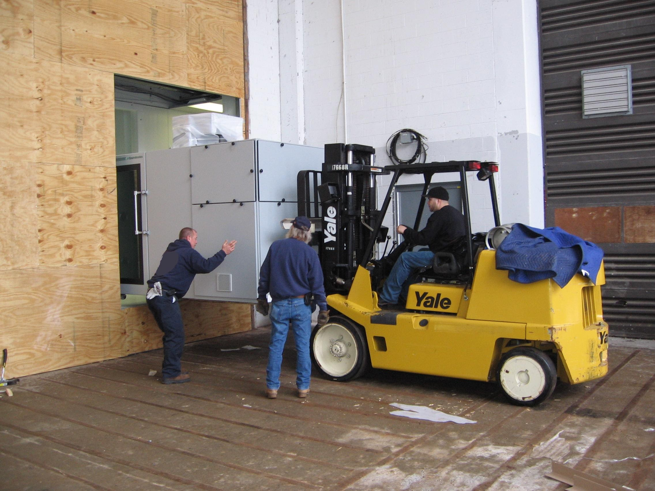 forklift moving large piece of equipment